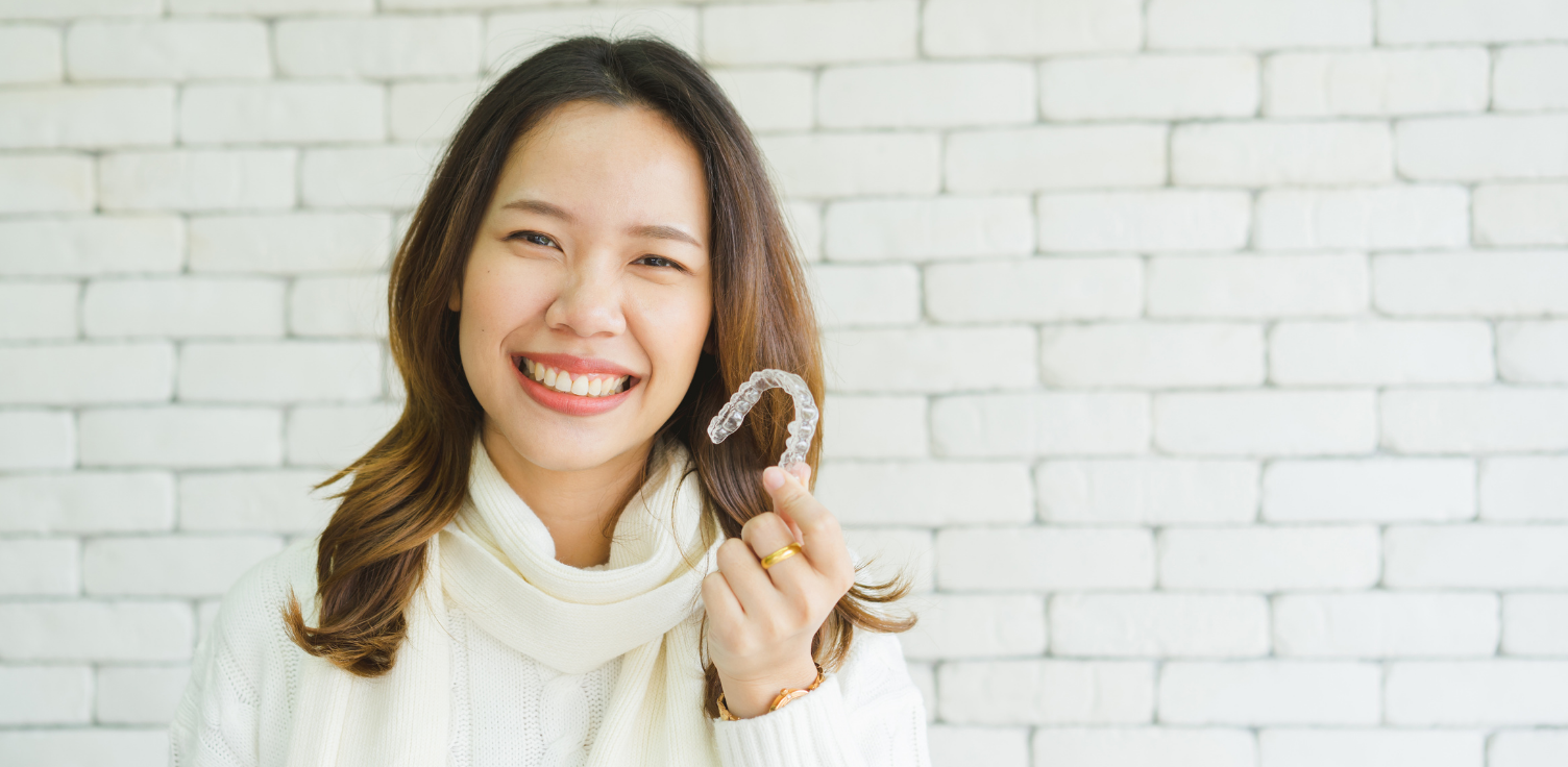 Lady smiling and holding clear retainer in hand