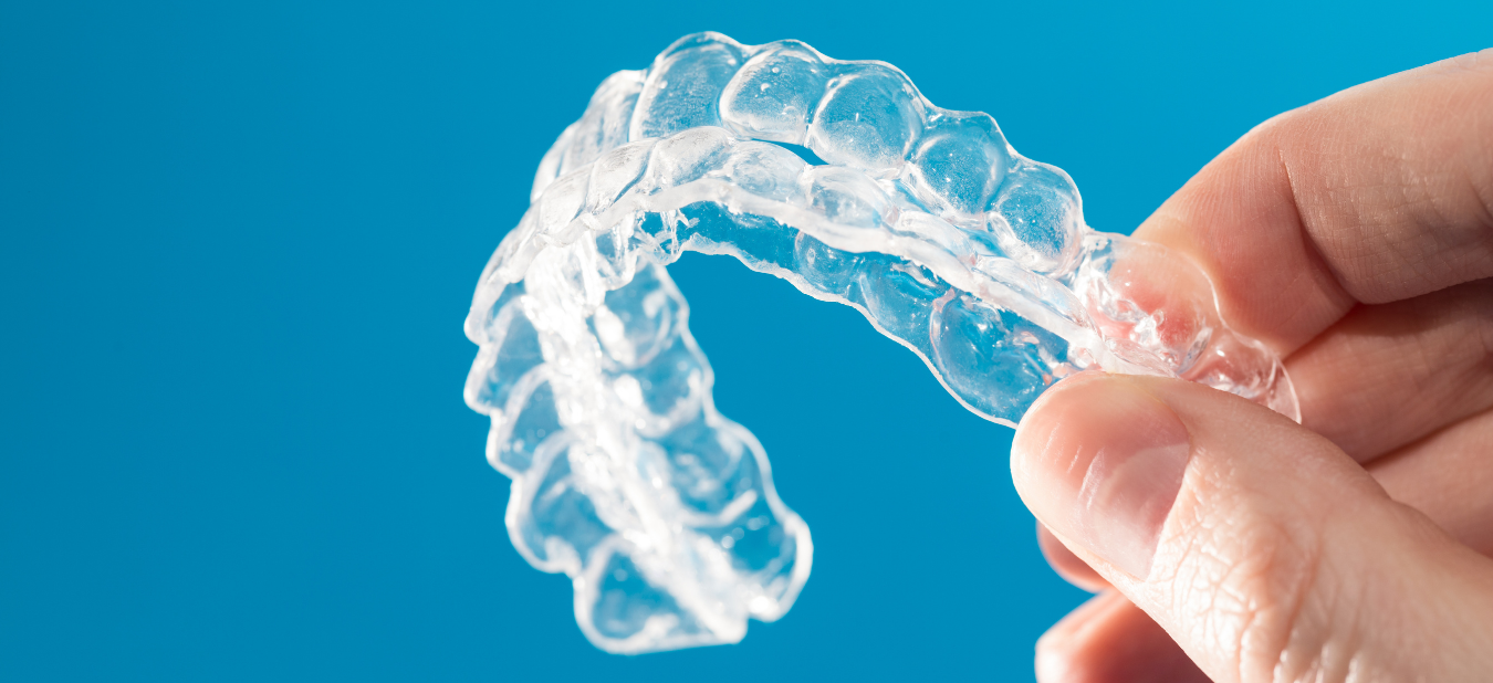 Person's hand holding Invisalign clear aligners