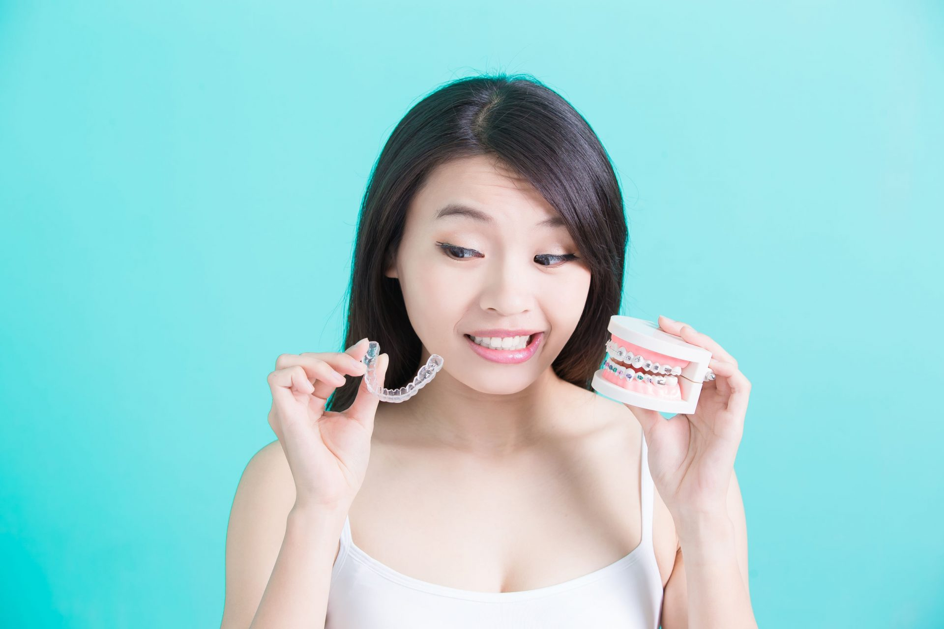 Woman holding Invisalign aligners and braces